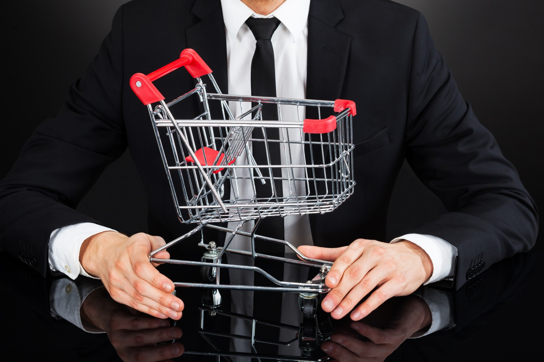 Businessman Holding Shopping Cart Model At Desk